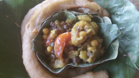 The food was a savoury donut, with chickpea and veg. curry, served on a banana leaf plate.